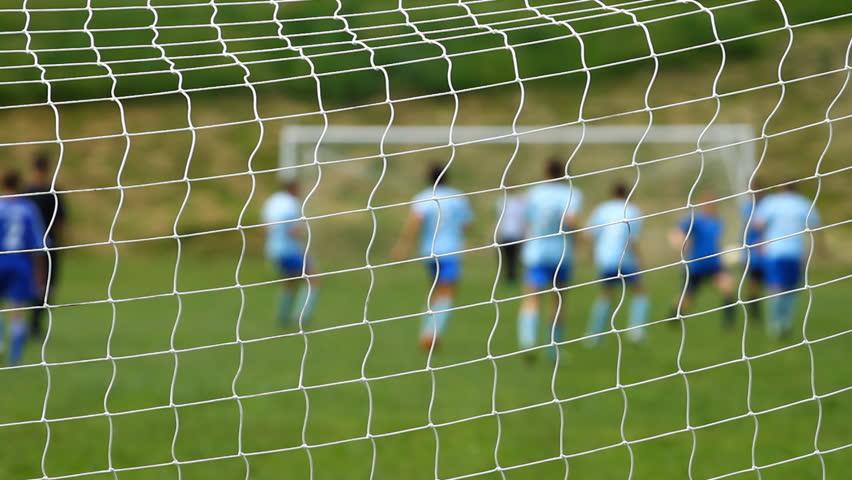 Children soccer game from behind goal net