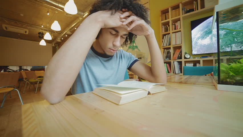 Attractive young man reading a book, he holds his head.  The guy looks very focused and serious  | Shutterstock HD Video #6462494