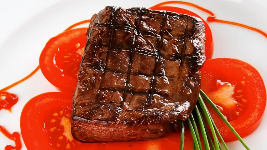 grilled beef meat entrecote fillet served with tomatoes and green chives china plate 1920x1080 intro motion slow hidef hd - HD stock footage clip