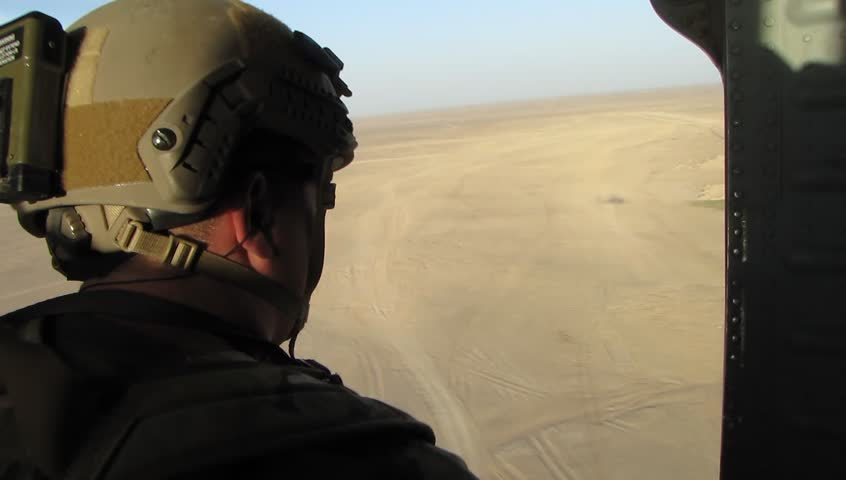 US soldier in helmet and combat armor sits in open doorway of military helicopter flying over desert in middle east