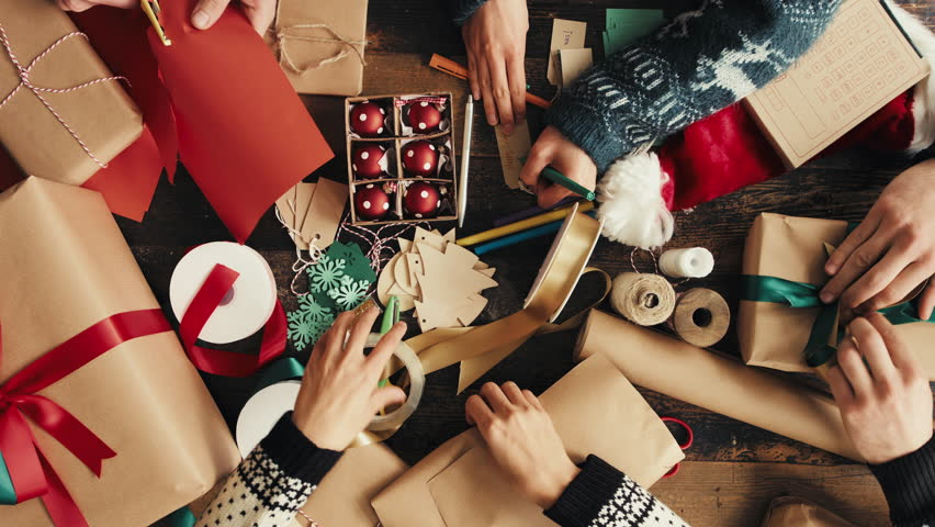 Hands wrapping Christmas presents arial view group of young diverse people