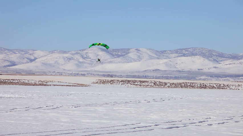 Powered parachute flying over ice and snow covered lake in winter. Central Utah winter recreation and sport. Pilot in aircraft. - HD stock video clip
