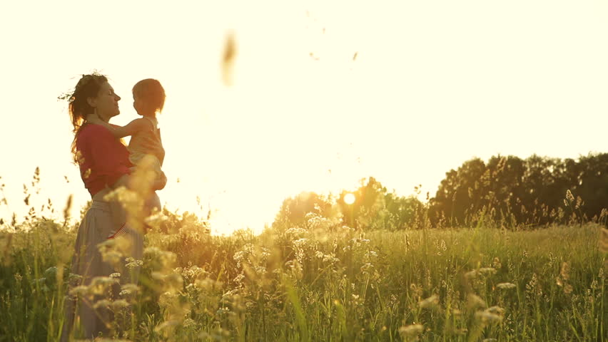 Young pregnant woman holding a baby daughter. Beautiful sunset in the meadow. Dolly shot. - HD stock footage clip