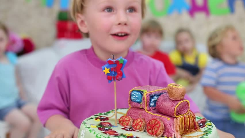 Little cute boy blows out candle on cake and claps and other kids look at he at children party. Focus on boy, cake