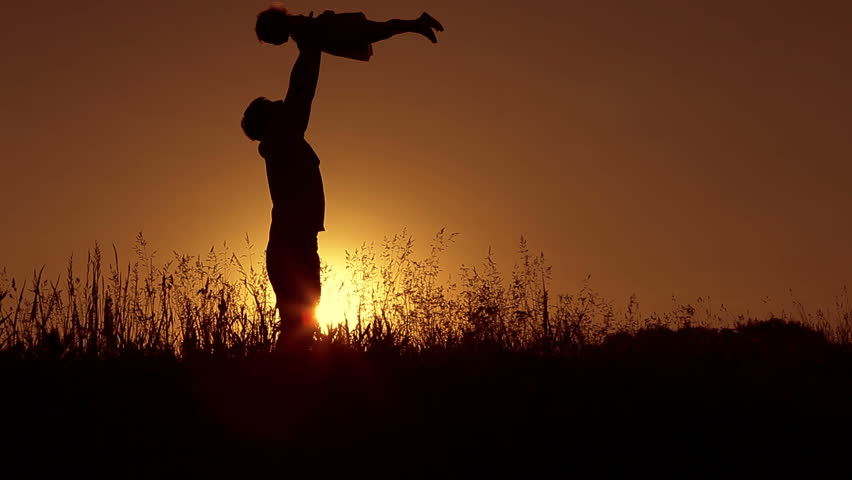 Father playing with little daughter at sunset. He throws her up and hugs. Dolly shot.