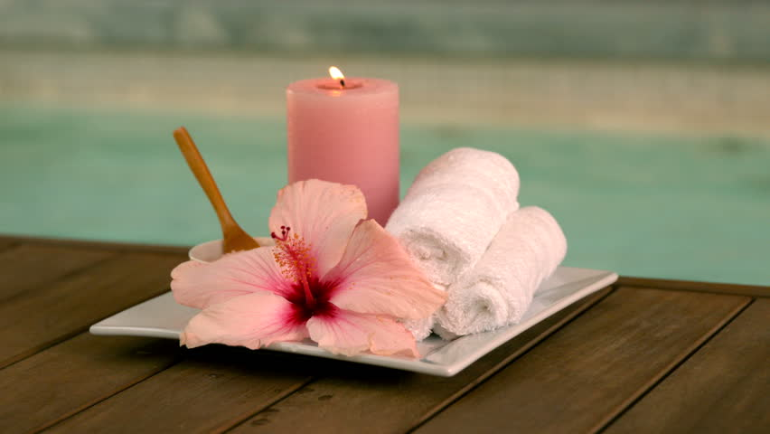 Beauty treatments and candle poolside with lily in slow motion - HD stock footage clip