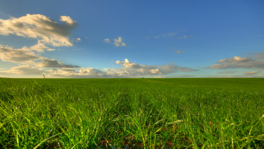 Sunset clouds over green field, hd motion time lapse clip, high dynamic range imaging