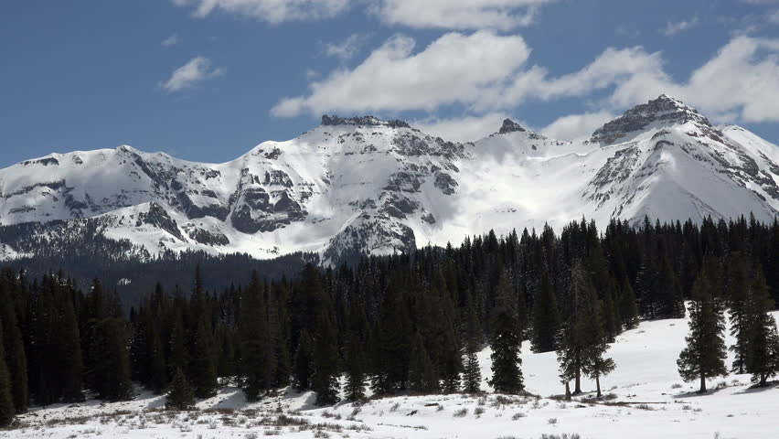 Rocky Mountains snow peaks clouds fast time lapse. Beautiful mountains near Telluride, Colorado. Spring time with snow and forest in nature. Clouds drifting along top of Rocky Mountain peaks.
