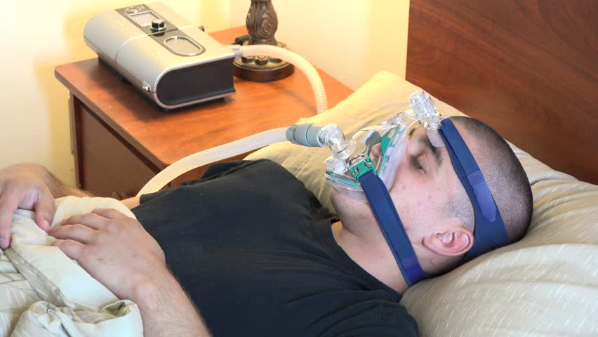 Man suffering from sleep apnea and wearing a cpap mask while sleeping, respiratory disorder or condition treated successfully by attaching a piece of equipment to the person with the problem.