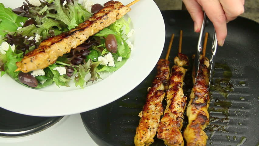 Grilled chicken kabobs being served from a griddle pan with tongs on to a plate with salad.
