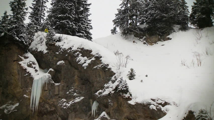 Skier carves down a ridge, causing snow to fall over the edge the whole way down the rockface,