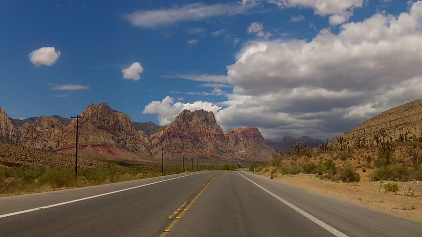 The point of view of someone driving a car on Red Rock Canyon Road in the Red Rock Canyon National Conservation Area in Nevada.  This area is overseen by the U.S. Bureau of Land Management.