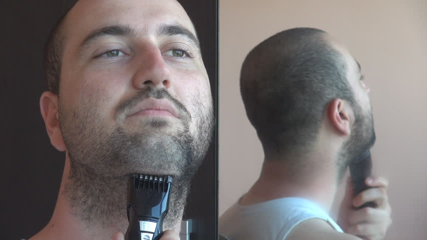closeup young caucasian man dry shaving his beard with an. Black Bedroom Furniture Sets. Home Design Ideas