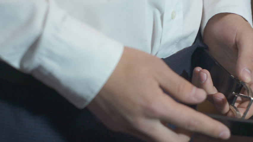 Man, male, boy, closeup unzips his trousers belt. The man is going somewhere. Closeup of hands fastening belt of his trousers. - HD stock footage clip