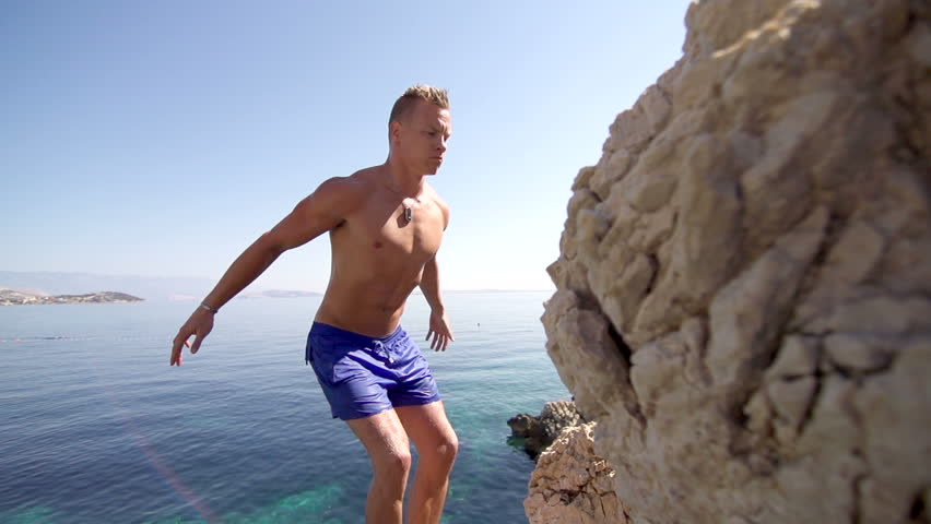 Spectacular Slow Motion Shot Of A Muscular Young Man Jumping Off A Cliff Doing A Back Flip Into Clear Blue Water. Sun Flares.