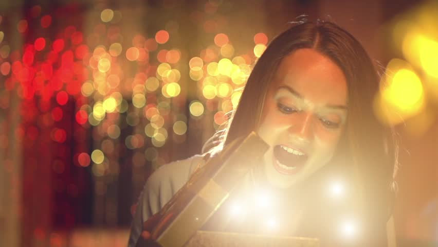 Beauty girl opens Christmas gift box with miracle lights. Surprised woman getting magic gift. Slow motion video footage 1080p. High speed camera shot 240 fps