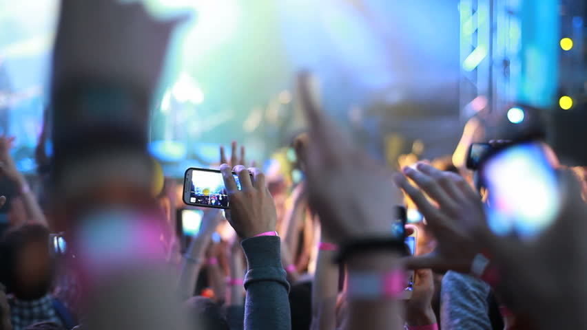 Fans waving their hands and hold the phone with digital displays the crowd at a rock concert. | Shutterstock HD Video #6663527