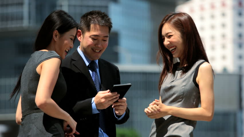 Upper body young male female Asian Chinese business team using wireless tablet hot spot developed urban area outdoors modern downtown city environment | Shutterstock HD Video #6677729
