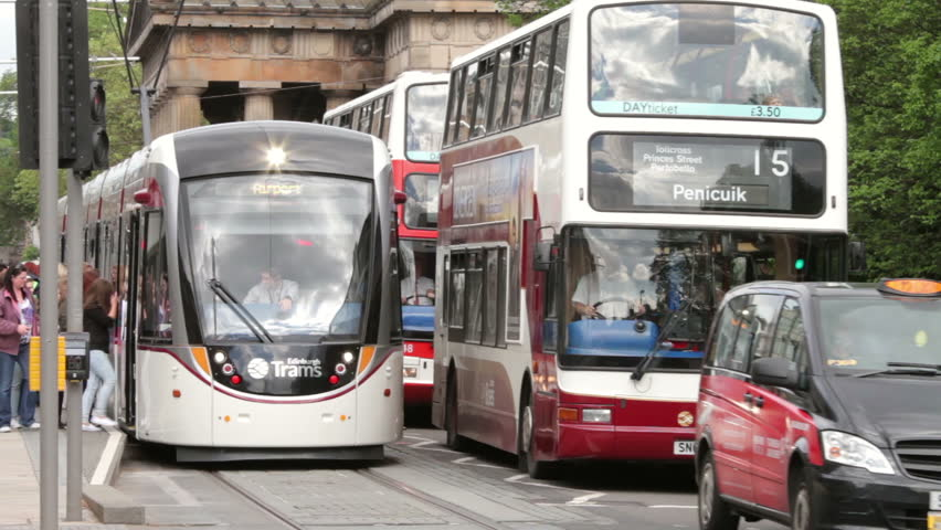 EDINBURGH, SCOTLAND - JUNE 03, 2014: Unidentified people wait at tram platform with heavy traffic passing by, Princes Street. The Edinburgh trams system opened in May 2014 at a cost of £1 Billion.