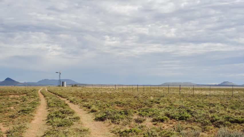 Linear timelapse, right to left at 45 degree angle down, shooting a typical Karoo farm scene with a gravel road and windmill in the distance. - HD stock video clip