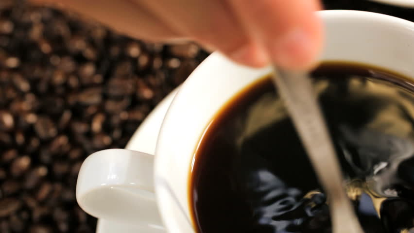 Close Up Female Hand Stirring Cup Black Coffee - Close up Caucasian female hand using spoon to stir freshly brewed ground black coffee white cup saucer beside whole coffee beans