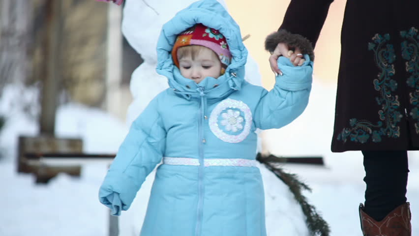 Mother shows the child a snowman - HD stock video clip