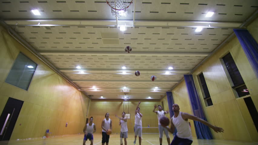 Competitive basketball players, playing on indoor court.