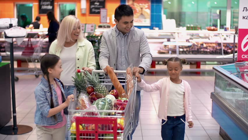 Pull back of family in supermarket strolling with shopping trolley full of products joyfully chatting