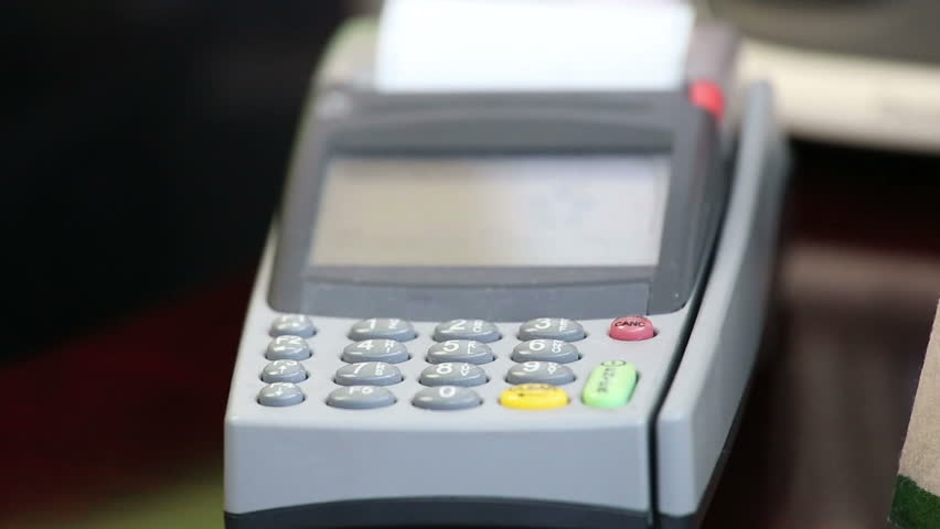close up image of a credit card being swiped through a card machine.