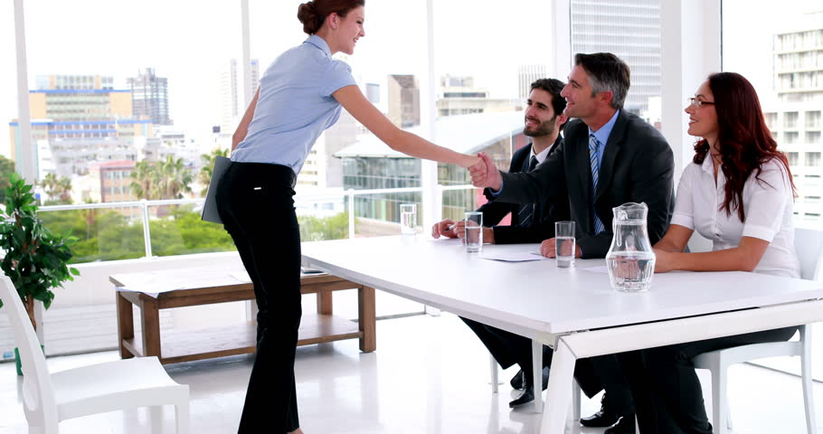 Interview panel speaking with young applicant and shaking her hand in the office