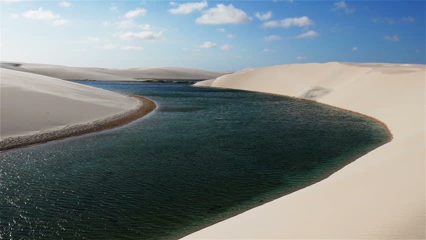 Dunes and Lagoons. A vertical pan to reveal the unique geography of sand dunes and fresh water lagoons found in Brazil's Lencois Maranhenses National Park.