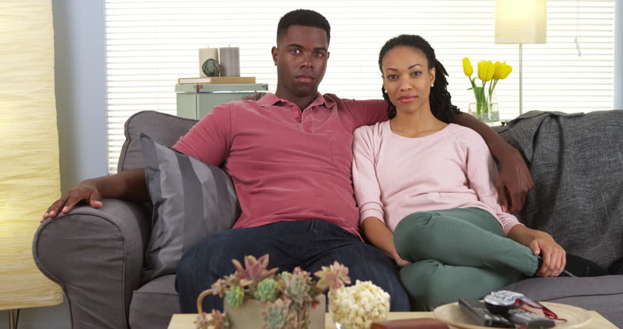 Attractive young black couple sitting on couch looking at camera - 4K stock footage clip