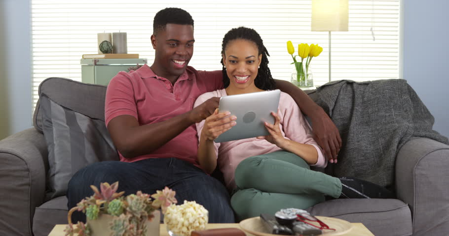 Smiling young black couple using tablet computer on couch - 4K stock video clip