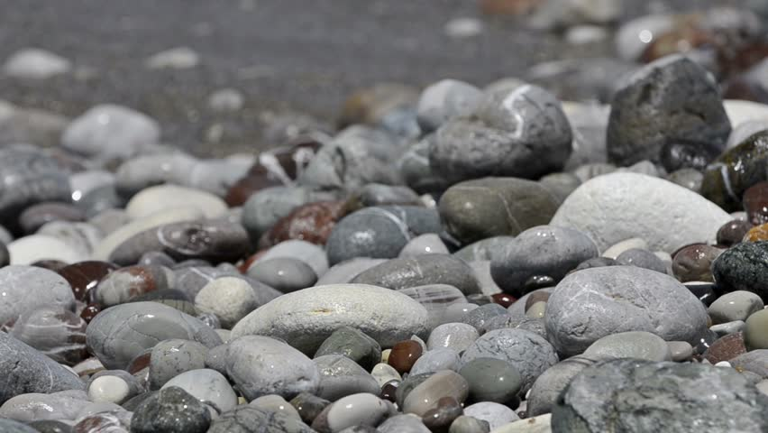 Sea waves roll on pebble beach. Close-up view real time - HD stock video clip