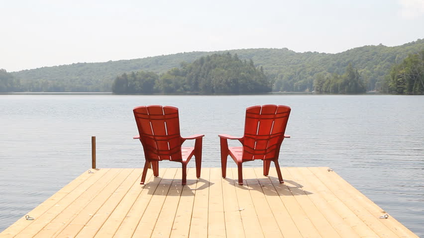 Two red chairs on cottage dock. Sunny morning. Medium shot.