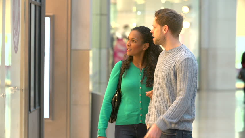 Couple Carrying Bags And Looking In Mall Shop Windows