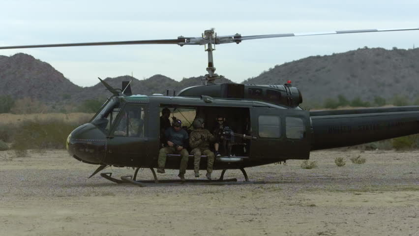 Huey helicopter taking off, with riders, the desert - HD stock footage clip