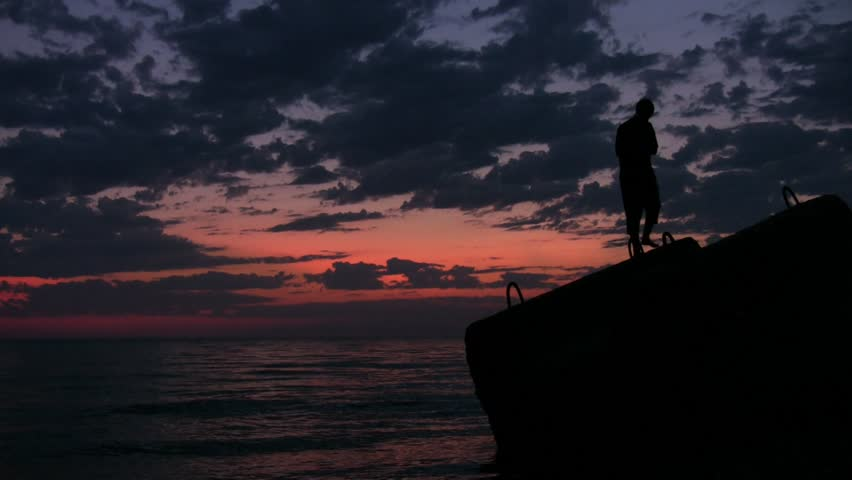 silhouette of young man walks on flagstone above sunset sea  - HD stock video clip