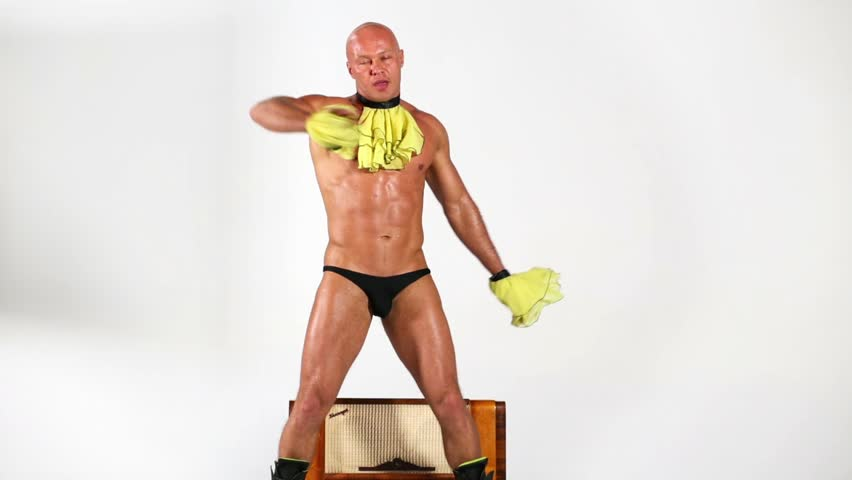 Bald muscular man dances around old radio-gramophone.