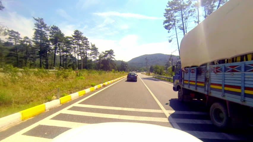 Cars overtaking the truck. Car driving on country road in a sunny day. Shot from car mounted camera.