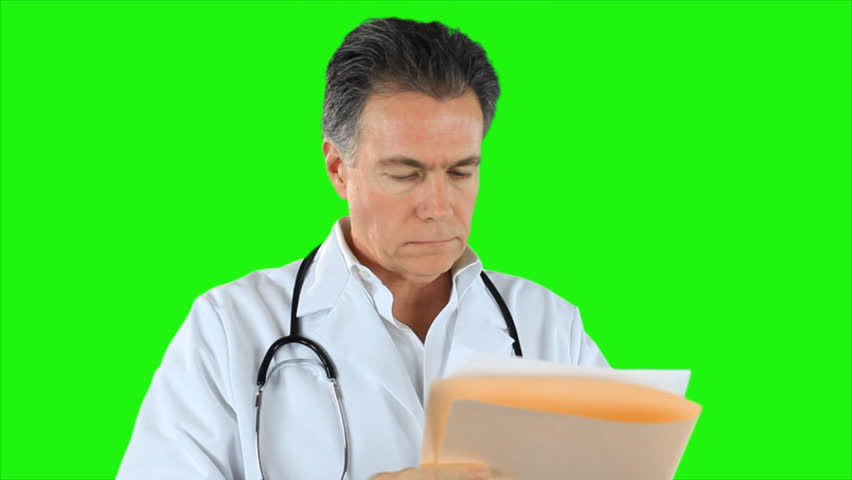 A doctor reading and making notes on a file he is holding. Green screen. - HD stock video clip