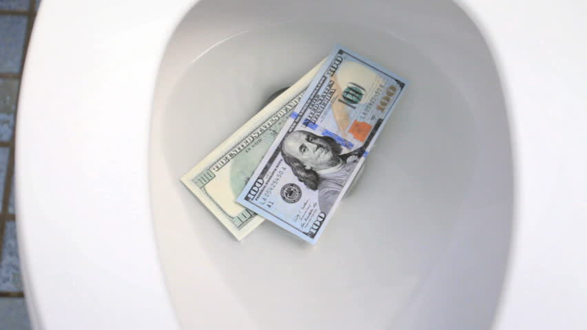 Cash flushing down toilet drain, wasting money concept