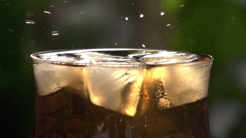 In a Glass with Ice Drops Fall. In a glass of sweet sparkling wine with ice cubes. It drops fall creating beautiful splashes. Slow Motion at a rate of 240 fps - HD stock footage clip