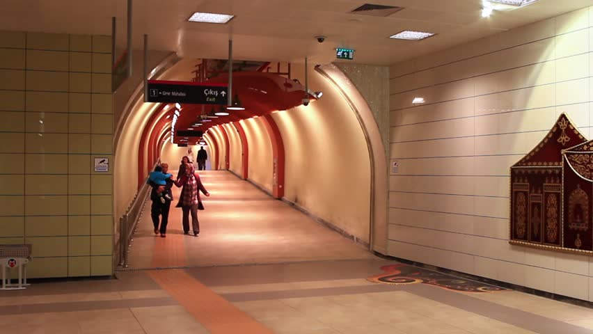 ISTANBUL - MAY 9, 2012: Underground passage with people walking from glowing end. Due to increasing traffic, air pollution, Istanbul became one of most polluted city also planned for turn to railway