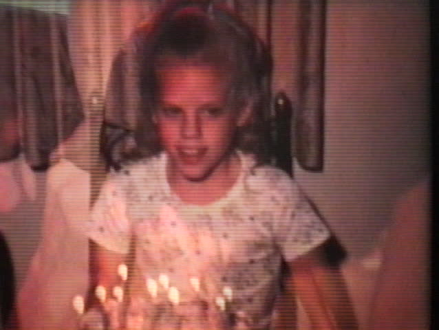 A cute little blond girl blows out the candles on her birthday cake as she celebrates turning ten years old.