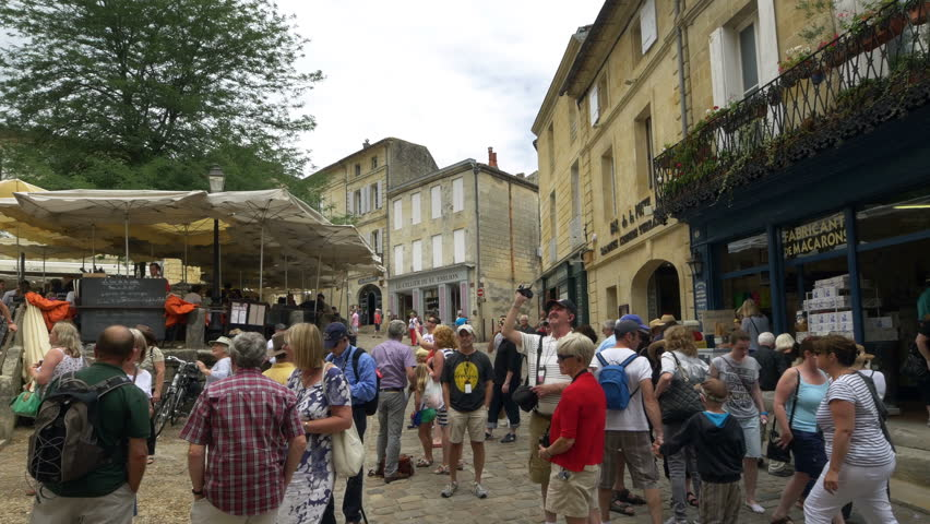 SAINT EMILION FRANCE - JULY 2014: A tour group in the Place de L'eglise Monolithe in the center of the town. This area is full of restaurants and wine shops and is always crowded with tourists.