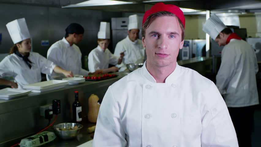 4K Portrait of a young trainee chef or worker in a commercial kitchen