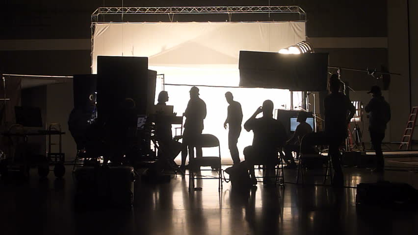 Unrecognizable film and photo crew working on professional studio shoot.