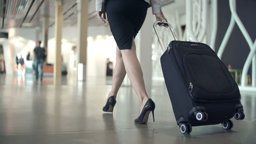 Low section of business woman walking with her back to the camera along airport waiting room in slow motion
