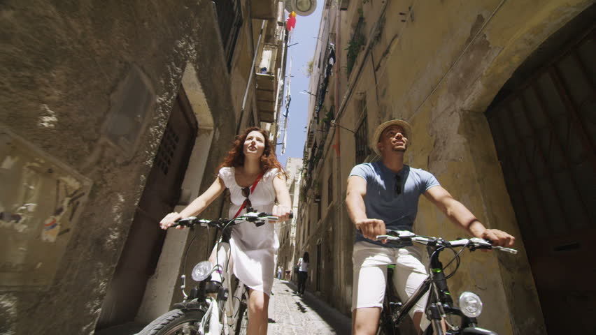 Attractive Couple Cycling In Small Italian Town And Having